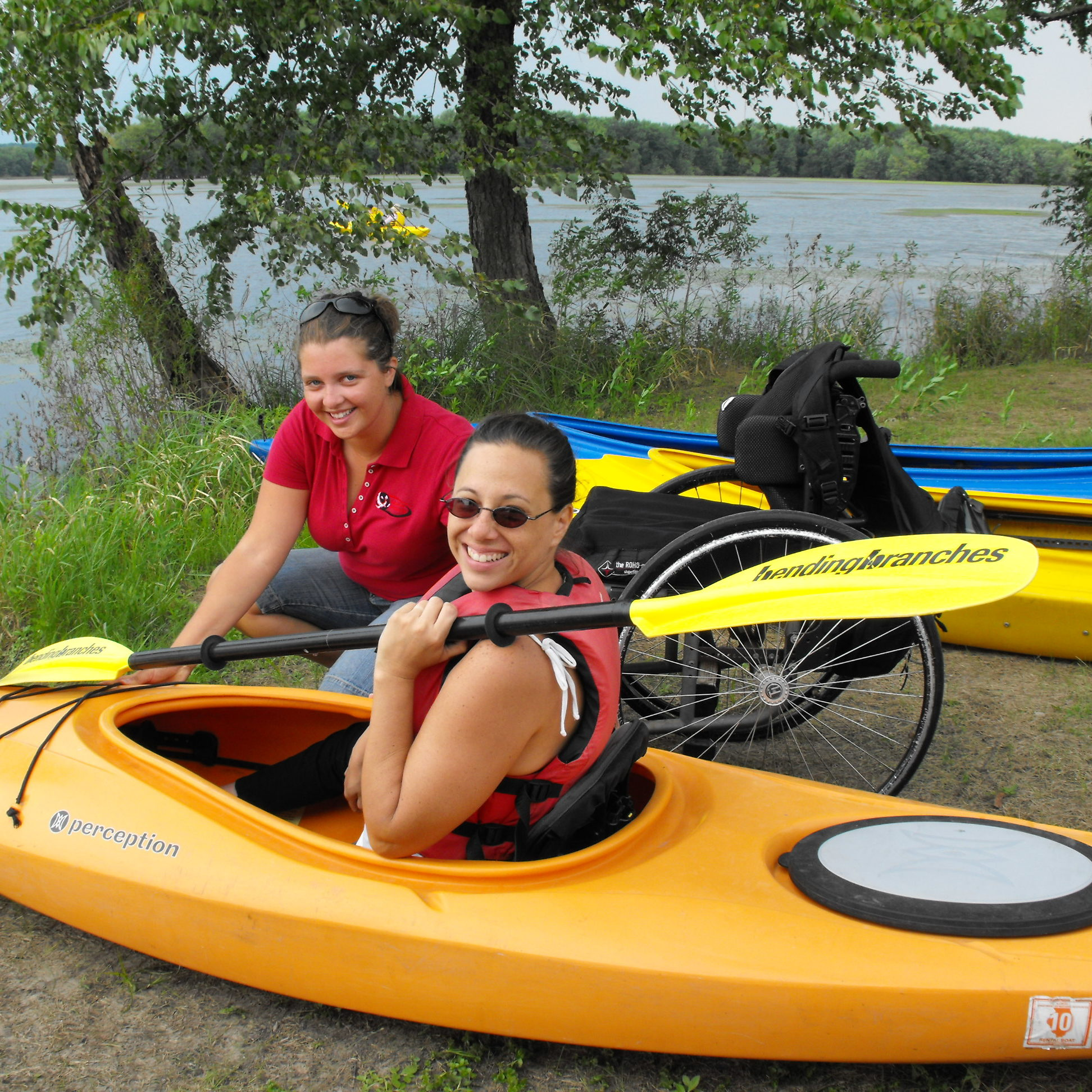 Volunteer helping adaptive kayaker